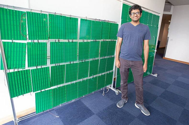 Lead author Venkat Arun in front of the RFocus smart surface prototype. Photo by Jason Dorfman, MIT.