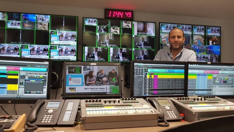 Elad Harel, Head of Playout Systems at IPBC, standing behind the Marina system interface screen.