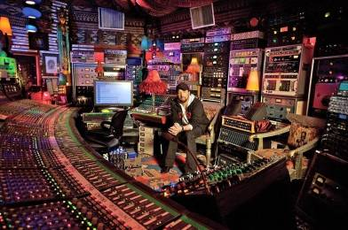 Producer Jack Joseph Puig surrounded by hardware components in his studio.