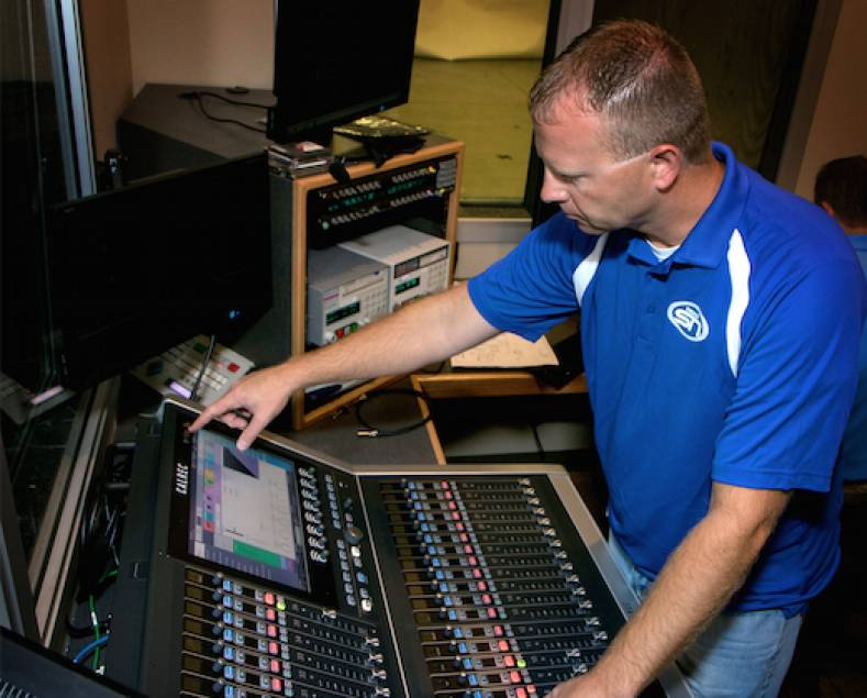 "Eric Vasgaard, MidcoSN Executive Producer and A1, at work on the Calrec Brio console aboard their new ""Lewis"" van."