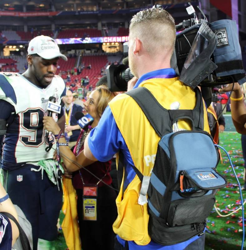 NESN photographer Patrick Gamere uses a LiveU unit as NESN reporter Elle Duncan interviews Chandler Jones of the Patriots after SB49