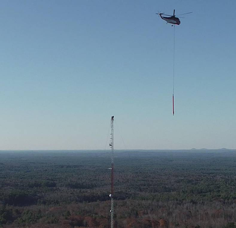 Helicopter lifts a new Dielectric TFU antenna to the WMEA tower. The station leveraged repack to triple TPO on its new channel.