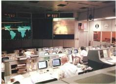 Gene Kranz (foreground, back to camera), an Apollo 13 Flight Director, watches Apollo 13 astronaut and lunar module pilot Fred Haise onscreen in the Mission Operations Control Room, during the mission's fourth television transmission on the evening of April 13, 1970. Shortly after the transmission, an explosion occurred that ended any hope of a lunar landing and jeopardized the lives of the crew. Click to enlarge. Image NASA.