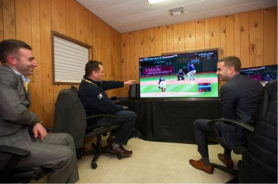 Delighted Fox Sports executives Jonathan Butnick, left, Mike Davies, center, and Eddie Motl, right, watch the Wednesday night game over the air on an ATSC 3.0-equipped 65-inch LG OLED TV.