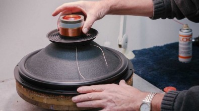 Worker assembling voice coil and cone onto speaker frame. Image: Volt Loudspeakers.