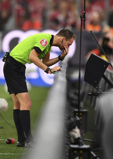 Referee Bastian Dankert consults a video monitor and communicates over his Bolero S belt pack at the FC Bayern Munich-Hoffenheim match in August 2018.