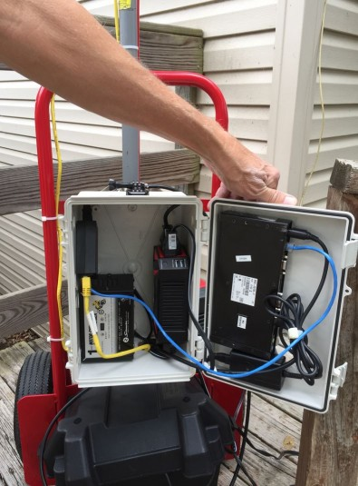 A weatherproof box on the hand truck contains power distribution and charging, and it protects electronic components not designed for outdoor use.