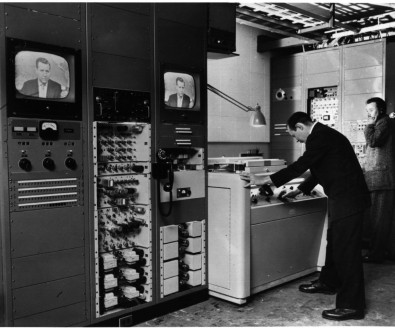 CBS was the first on-air user of a video tape recorder, VTR. The machine was first used to tape-delay the evening CBS News broadcast with Douglas Edwards on Nov. 30, 1956.<br /><br />In this photo, CBS Engineer John Radis inspects playback of an evening news broadcast from an Ampex quadruplex videotape recorder at CBS Television City in Hollywood.<br /><br />Jim Morrison is on the phone to the right of VRX-1000 transport, one of only 16 hand-built machines. The two racks of tube equipment to the left contain the electronics for the recorder.<br /><br />Courtesy Quad Videotape Group.