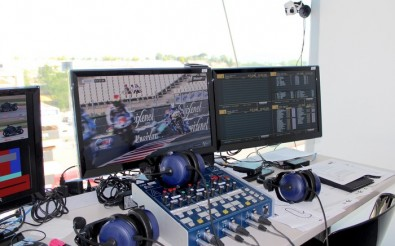 Commentary booth with control desk (centre) and mini-camera (top-right corner).