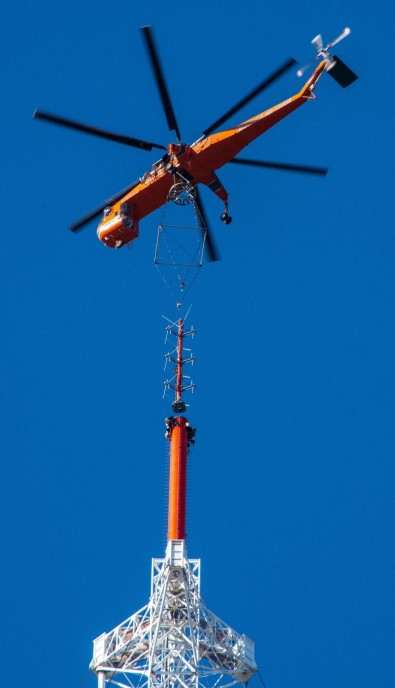 A Sikorsky Skycrane hoists a 3 bay Dielectric TDM antenna to top the American Tower in Needham MS for WGBH-TV (Rf Ch 05). The TUM antenna beneath it is for WBZ-TV, WCVB-TV, WGBX-TV, WSBK-TV, and WFXT, interim for all but WFXT.