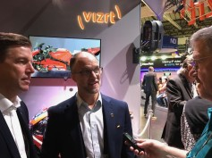 Vizrt president, Daniel Nergard (left), and product director, James Stellpflug (center), talk with Jay at their exhibit during IBC 2019.