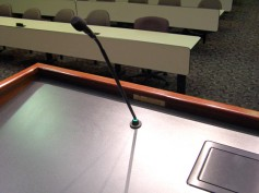 A lav-size microphone used on a podium provides easy installation and minimal image blockage to cameras and audiences. Click to enlarge.